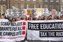 "Students marching with banners that read ""free education - tax the rich"""
