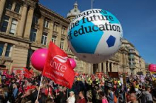 "A photograph of a trade union demonstration, central in the photograph is a large NEU balloon with ""shaping the future of education"" written on it"