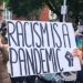 "A photo of protesters holding a placard which reads ""Racism is a pandemic"""